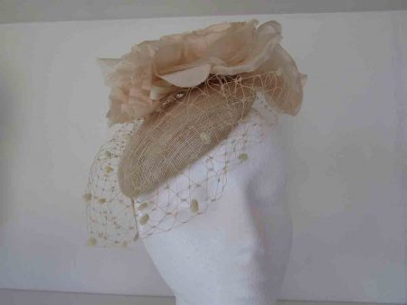Pillbox style with spot veiling and a large soft flower on the side in champagne