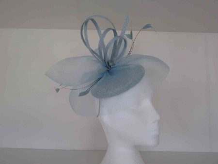 Sinamay topped with crin swirls and loops with diamond shaped feathers on an aliceband in light blue
