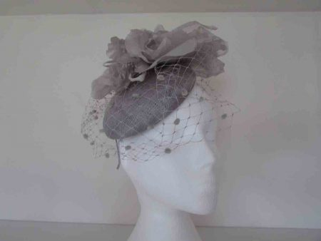 Pillbox style with spot veiling and a large soft flower on the side in silver