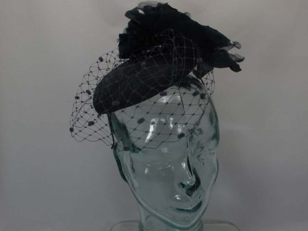 Pillbox style with spot veiling and a large soft flower on the side in Navy