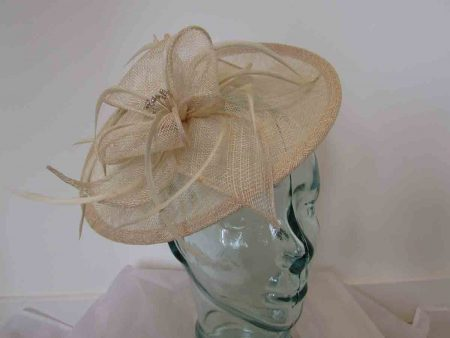 Hatinator with sinamay flower and diamante centre in champagne