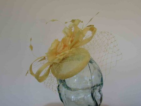 Pillbox fascinator with netting and flowers in lemon yellow