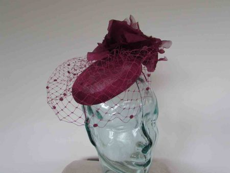 Pillbox style with spot veiling and a large soft flower on the side in plum
