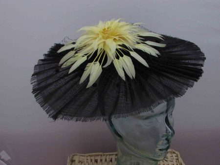 Black circular fascinator with yellow flower