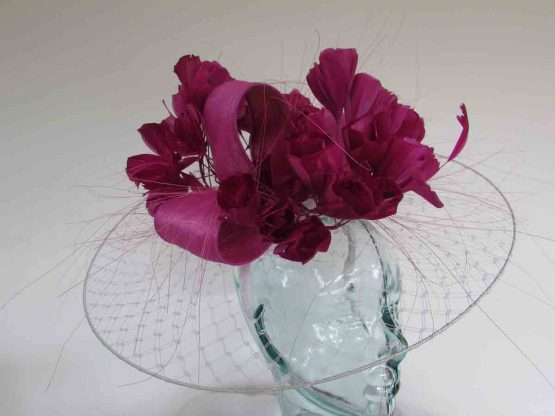 Veiling disc in white with small feathered flower in magenta pink